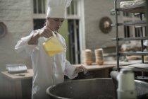 Female baker versant l'ingrédient dans la table de mixage — Photo de stock