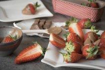 Placa de fresas en rodajas recubiertas de chocolate sobre superficie gris - foto de stock