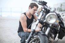 Байкер перевірка мотоцикла при дорозі — стокове фото