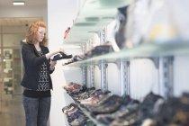 Женщина смотрит на сандалии — стоковое фото