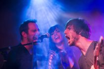 Rock band performing on stage in night club — Stock Photo
