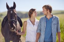 Jeune couple marchant avec cheval en campagne — Photo de stock