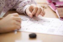 Schoolgirl working on work sheet in classroom — Stock Photo