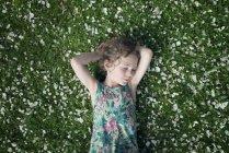 Маленькая девочка лежит на лугу с разбросанными яблочными цветами — стоковое фото