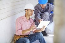 Construction worker and foreman using digital tablet — Stock Photo