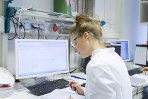 Technicien de laboratoire avec dossier de travail à l'ordinateur — Photo de stock