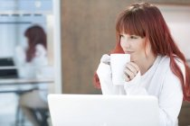 Young woman with laptop and cup of coffee in kitchen — Stock Photo