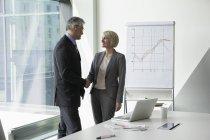 Businissman et femme d'affaires, se serrant la main dans la salle de conférence — Photo de stock