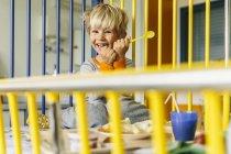 Portrait of happy little boy sitting in bed having breakfast — Stock Photo