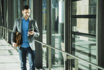 Young businessman walking and using cell phone — Stock Photo