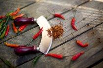 Cialde di peperoncino rosso e verde, mezzaluna e peperoncino in polvere su legno — Foto stock
