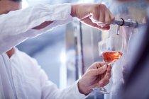 Fabricante de vinho batendo vinho do tanque — Fotografia de Stock