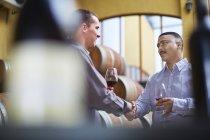 Виноделы дегустируют вино в винном погребе — стоковое фото