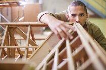 Молодой строитель рассматривает конструкцию балки крыши — стоковое фото