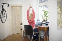 Женщина, сидящая за столом в своей мастерской, растягивается — стоковое фото