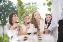 Waiter presenting bottle of red wine to women on a wine tasting session — Stock Photo
