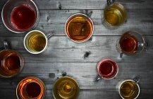 Vista superior de vasos de té con distintos tipos de té - foto de stock