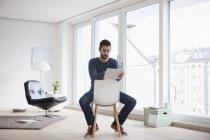 Giovane che si siede sulla sedia nel suo salotto utilizzando la tavoletta digitale — Foto stock
