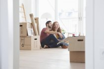 Young couple in new flat with cardboard boxes — Stock Photo