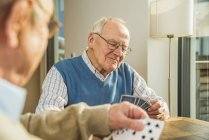 Two senior friends playing cards at home — Stock Photo