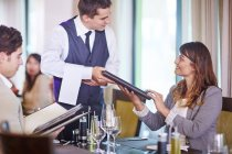 Business people placing order with waiter at hotel restaurant — Stock Photo