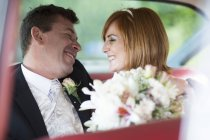 Close-up of Happy bride and groom sitting in car — Stock Photo