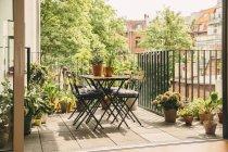 Chaises de Bistro et table sur balcon avec vue dans l'yard pendant la journée — Photo de stock