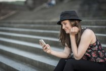 Germany, Koblenz, Deutsches Eck, young woman with cell phone sitting on stairs — Stock Photo