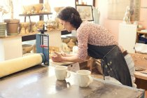 Potter in workshop working on earthenware cups — Stock Photo