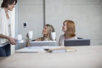 Three businesswomen drinking coffee in conference room — Stock Photo