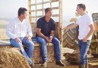 Wine growers sitting on trailer, taking a break — Stock Photo