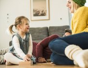 Family playing game on wooden floor — Stock Photo