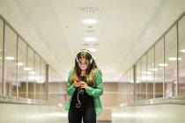 Молода жінка з навушниками і смартфонів — стокове фото