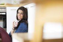 Junge Frau mit Tasse Kaffee entspannt in Küche — Stockfoto