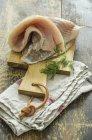 Fresh coalfish with dill on chopping board — Stock Photo