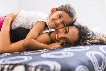 Портрет улыбающейся девочки-подростка и ее младшей сестры, лежащей на кровати — стоковое фото
