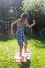 Девушка развлекается с надувной подушкой для воды в саду — стоковое фото