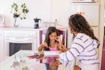 Teenage girl drawing with her little sister at table — Stock Photo