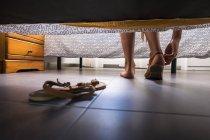 Дівчинка-підліток надягаючи сандал, перегляд під ліжком — стокове фото