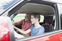 Father teaching son driving a car, side view — Stock Photo