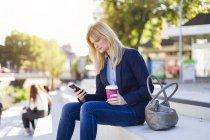 Блондинка предприниматель идти на смартфон с кофе — стоковое фото