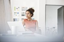 Woman sitting at office desk with computer thinking, looking aside — Stock Photo