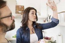 Skeptische Frau in Küche hält Glas — Stockfoto