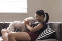 Young woman at home caressing her dog — Stock Photo