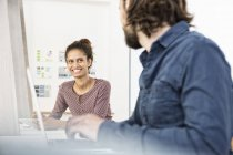 Smiling woman looking at colleague in office — Stock Photo