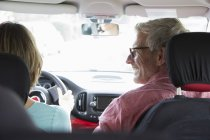 Happy mature couple driving car, rear view — Stock Photo