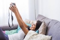 Happy teenage girl lying on couch taking selfie with camera — Stock Photo