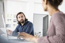Dos colegas en la oficina, uno frente al otro - foto de stock