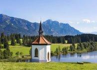 Германия, Бавария, Олгау, часовня на озере Хегратсрид с деревьями на берегу — стоковое фото