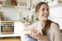 Mulher jovem feliz com café na cozinha — Fotografia de Stock